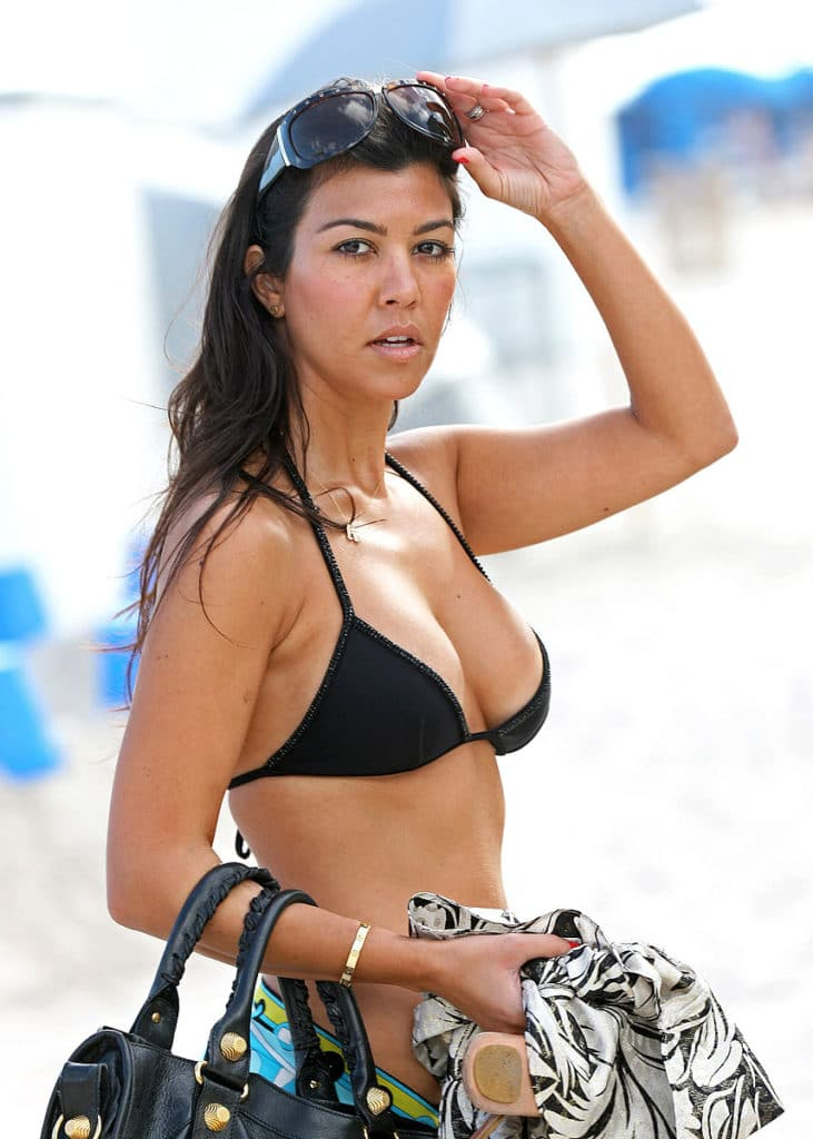 reality tv star kourtney kardashian in a black bikini top about to pull down her sunglasses