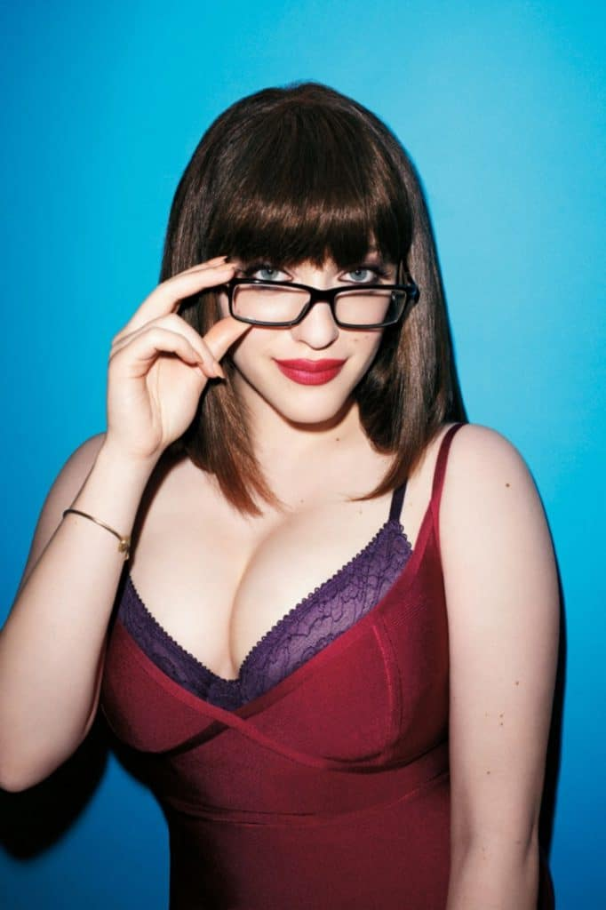 Kat Dennings looking sexy with thick rimmed back eyeglasses and showing off her cleavage