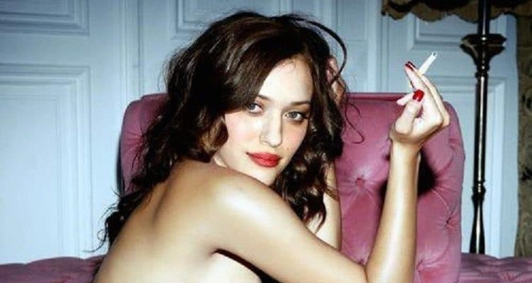 Kat Dennings smoking a cigarette topless and staring at the camera