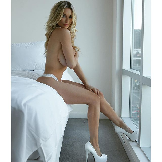 hot nude pic of lindsey pelas in white heels next to a window