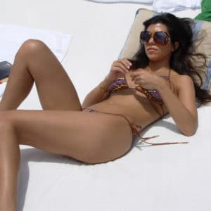 hot pic of kourtney kardashian in tiny bikini laying against a pillow with sunglasses on