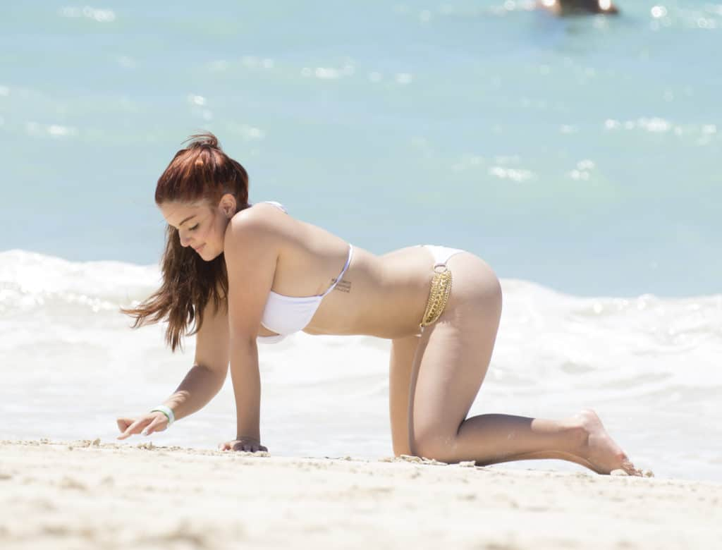 Ariel Winter writing in the sand at the beach