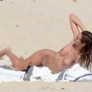 Model Edita Vilkeviciute lounging in the nude at the beach