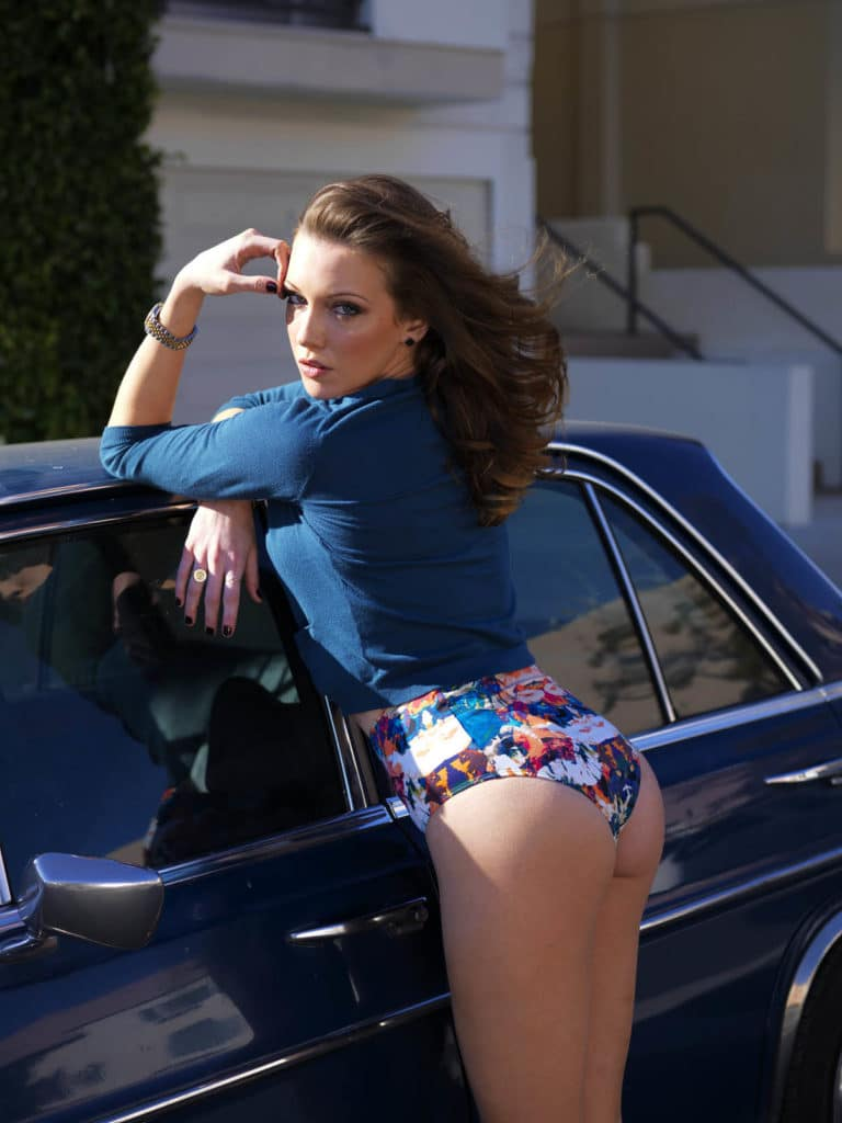 The singer Katie Cassidy leaning against car in flower print bottoms
