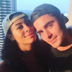 sami miro and zac efron with hats on backwards taking a selfie