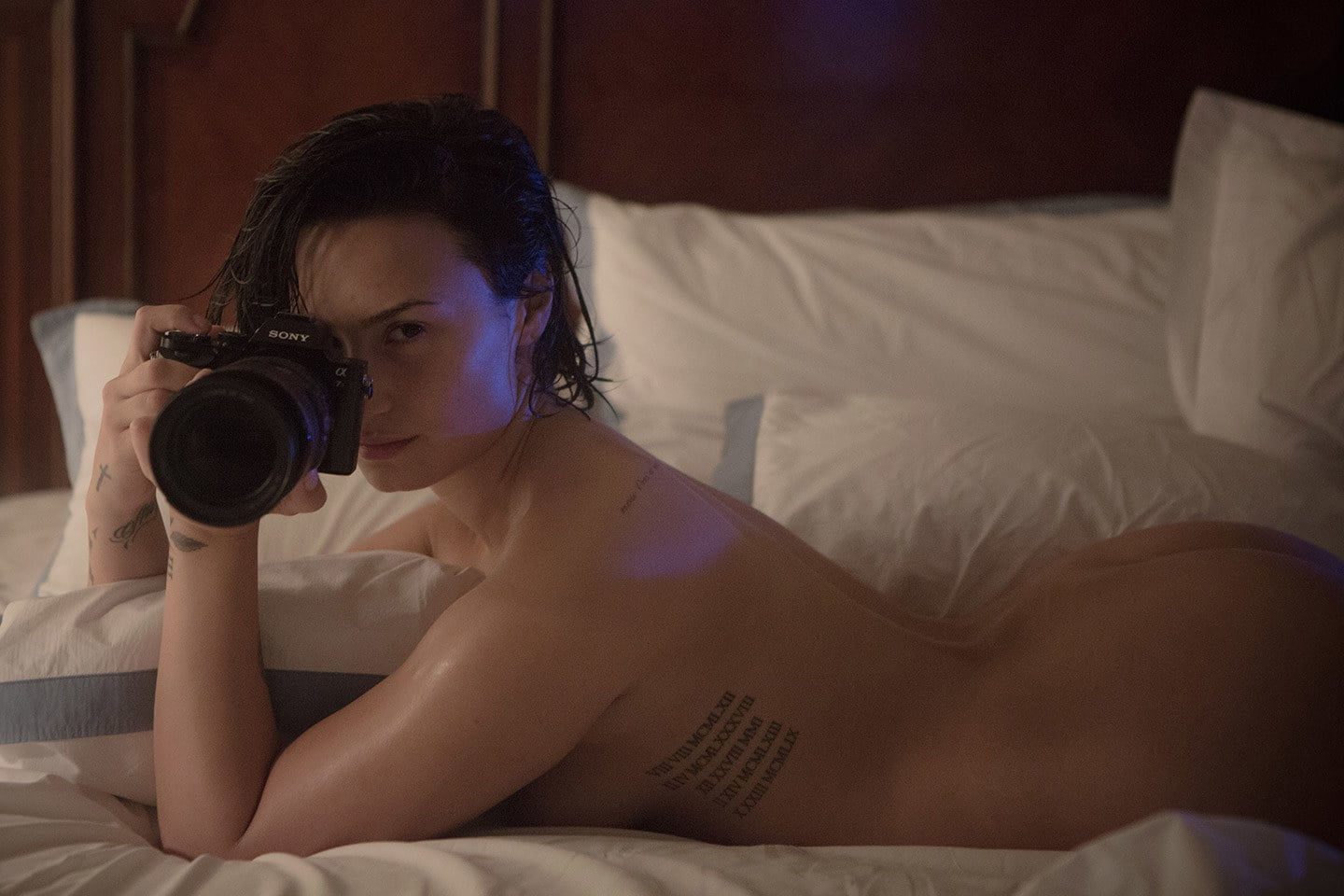 Demi Lovato on her back taking a naked selfie on a bed with a camera